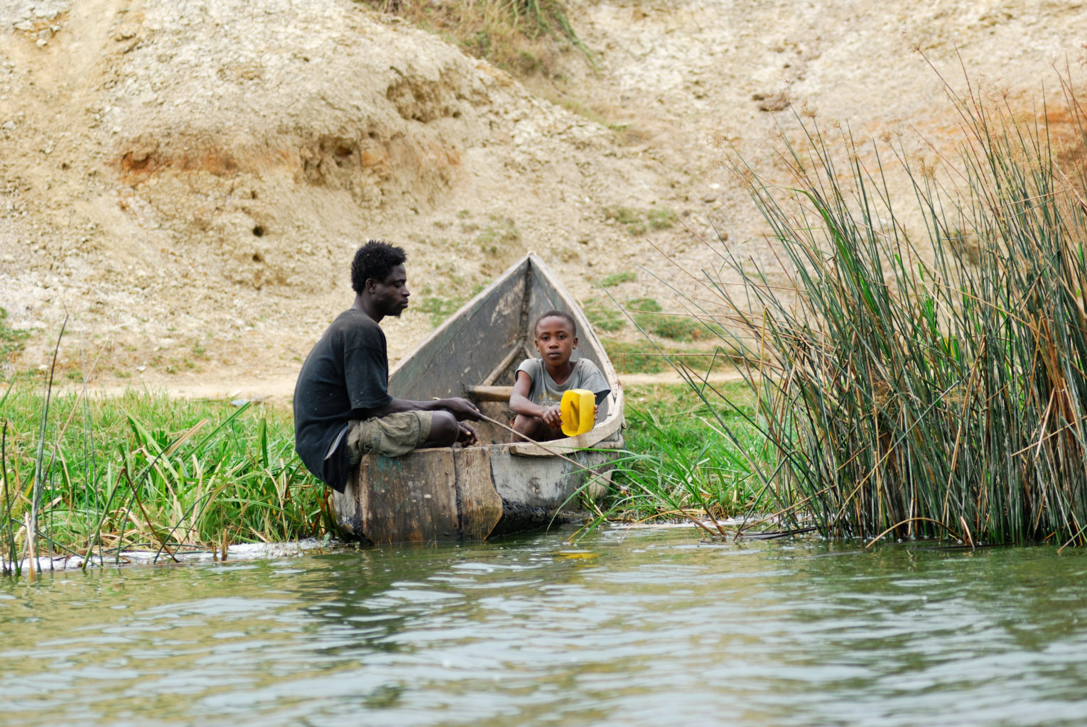 QUEEN ELISABETH NATIONAL PARK UGANDA - AUG 29 2010: Local fisherman and his son shown on the Kazinga channel shore. The Kazinga channel is the only source of transportation in this region of central Africa