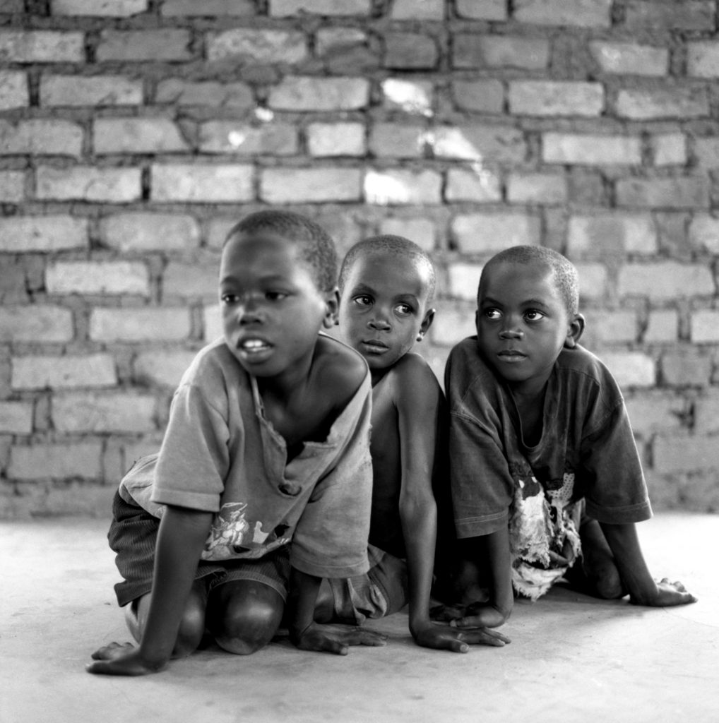 Three boys kneeling on a concrete floor with a brick wall in the background. Katebo Uganda. August 2004.
